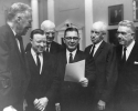 "Walter Reuther outside committee room, in group House Ways and Means on International Trade (HR9900).  ""Left to Right:  Christian Herter, Walter Reuther, unidentified, Rep. Wilbur Mills Omar Bradley, McNamara.""March 21, 1962"""