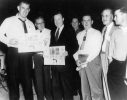 Walter Reuther holding up a newspaper with other UAW-CIO members at the 20th Constitutional Convention in Long Beach, California. May 1966
