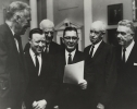 "Reuther outside committee room, in group House Ways and Means on international trade (HR9000).  Left to Rght:  Christian Herter, Reuther unidentified, Rep. Wilbur Mills, Omar Bradley, McNamara.""March 21, 1962"""
